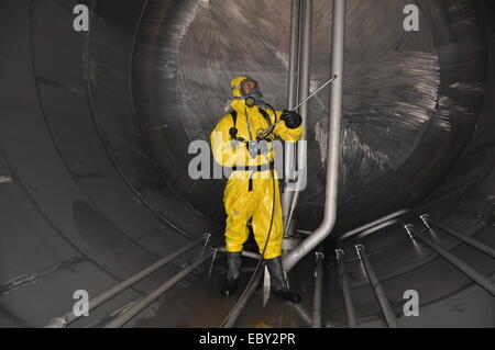 Man in chemical suit working  in tank of chemical tanker for cleaning operation - Stock Photo