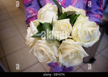 Bridesmaid holding a white bridal wedding bouquet - Stock Photo