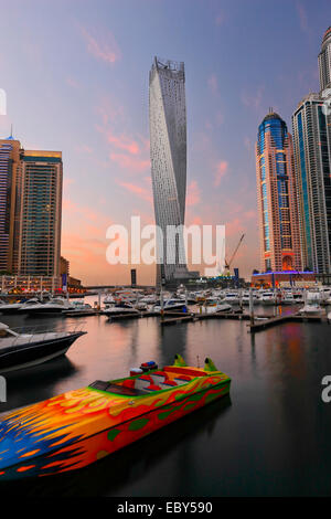 Dubai Marina skyline. Speed boat in front and twisted tower on the back. - Stock Photo