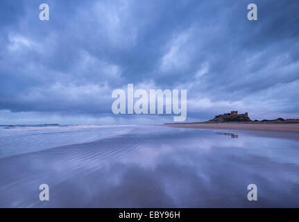 Stormclouds reflect on the deserted beach beside Bamburgh Castle, Northumberland, England. Winter (March) 2014. - Stock Photo