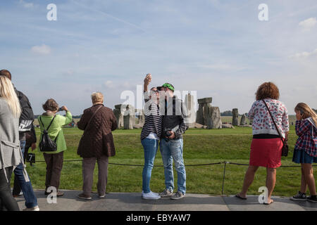 Couple take a 'selfie' of themselves in front of Stonehenge using a mobile phone. - Stock Photo