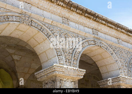 Elaborately carved stone arches in the cloisters on the exterior facade of the ancient Jesuit church, Iglesia de - Stock Photo