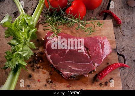 a beef steak on a wooden cutting board ready for the barbecue - Stock Photo