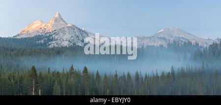 Unicorn Peak mountain above mist shrouded pine forest, Yosemite National Park, California, USA. Autumn (October) - Stock Photo