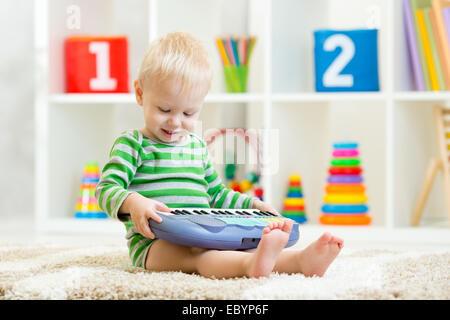 Happy little kid toddler boy having fun playing piano toy sitting on floor in nursery