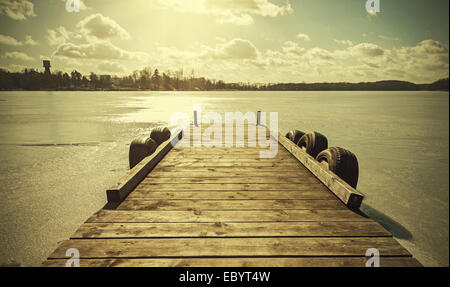 Vintage retro toned image of a pier on frozen lake. - Stock Photo