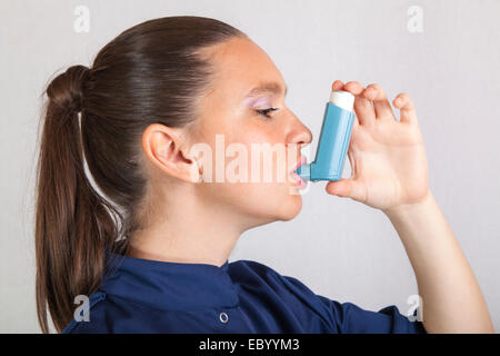 Cute nurse using asthma inhaler - Stock Photo