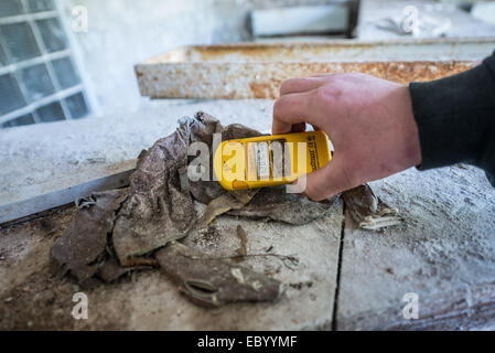 tourist checking radiation level in City Hospital No. 126 in Pripyat abandoned city, Chernobyl Exclusion Zone, Ukraine - Stock Photo
