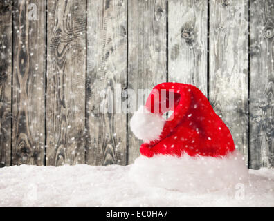 Christmas Santa Claus cap on snow with wooden planks as background - Stock Photo