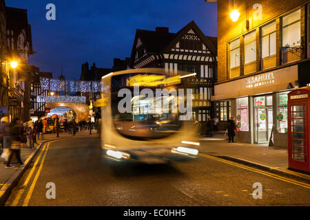 Public transport buses on the streets of Chester, Cheshire; City centre nightime landscape Christmas holiday shopping - Stock Photo