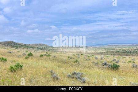 Open prairie, grassland, and dry scrub and hills under a bright sky near Vermilion, Nebraska, USA. - Stock Photo