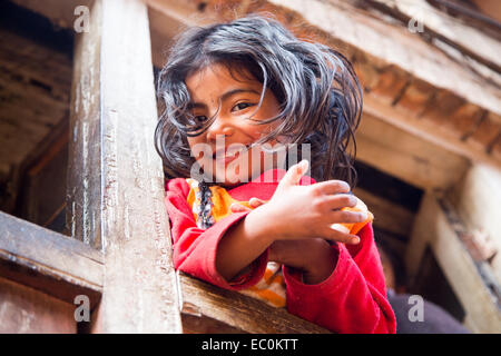 Young Napali girl in a window in Bhaktapur, Nepal - Stock Photo
