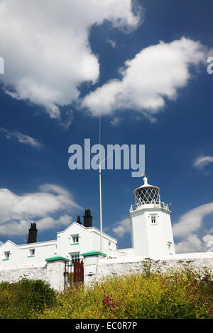 A white painted lighthouse with adjoining cottages. - Stock Photo