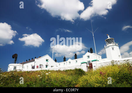 A white painted lighthouse with adjoining cottages and a black fog horn. - Stock Photo