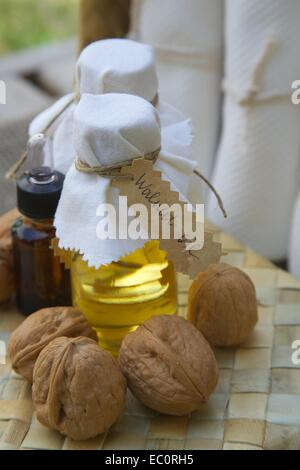 Bottle of walnut oil on the woven surface. Walnuts in the background - Stock Photo