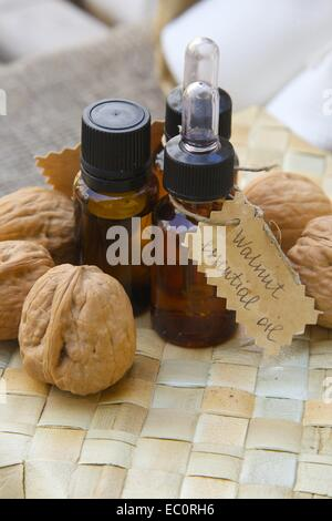 Bottle of walnut essential oil on the woven surface. Walnuts in the background - Stock Photo