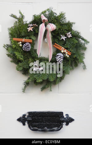 A Christmas wreath hangs on the white painted wooden front door of a traditional English country home in the Peak - Stock Photo