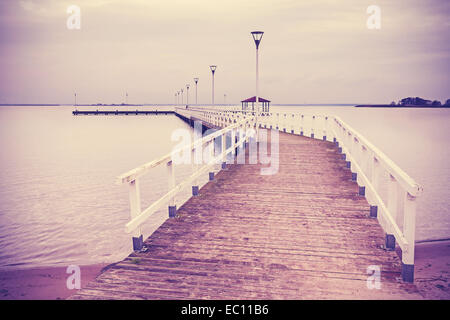Vintage retro filtered wooden pier at sunset. - Stock Photo