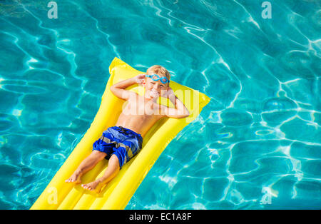 Young Boy Relaxing and Having Fun in Swimming Pool on Yellow Raft. Summer Vacation Fun. Relaxing Lifestyle Concept. - Stock Photo