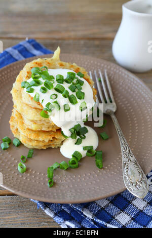 Potato pancakes with sour cream and green onions on a plate, on wooden boards - Stock Photo