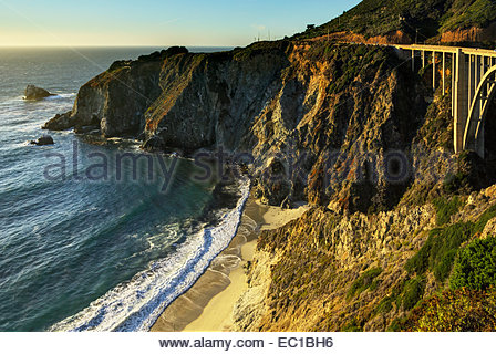 Bixby Bridge is a famous Cabrillo Highway (California One, coast road) landmark nearby house perched dramatically - Stock Photo