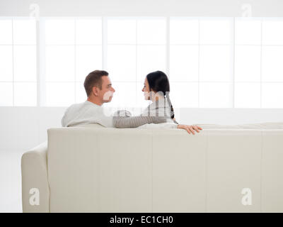 back view of young happy caucasian couple sitting on sofa in new house - Stock Photo