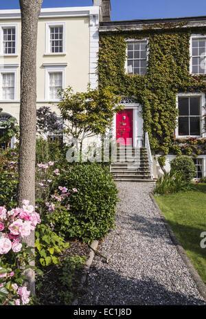 Georgian doorway and houses by the sea, Sandycove, Co. Dublin, Ireland, with rose garden - Stock Photo