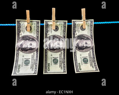 Three one hundred dollar banknotes hanging on laundry line attached with wooden clips over black background - Stock Photo