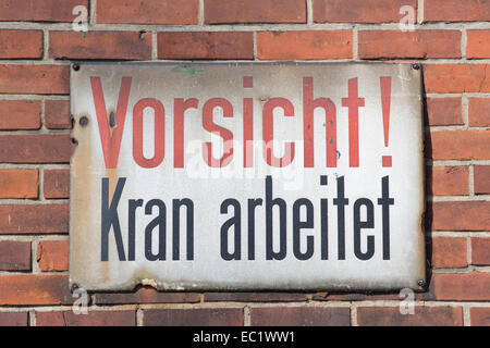 Vorsicht Kran arbeitet retro sign on brick wall - Stock Photo