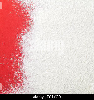 White wheat flour looks like snow on red paper background. Top view. Copy space - Stock Photo