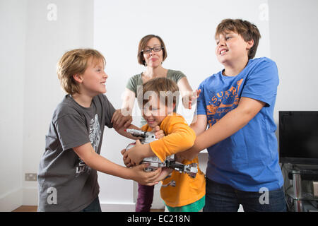 A mother trying to break up her children fighting at home Stock Photo