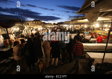 Street food:tourists waiting to eat in one of the several open-air restaurants in Djemaa El-Fna,Marrakesh,Morocco - Stock Photo