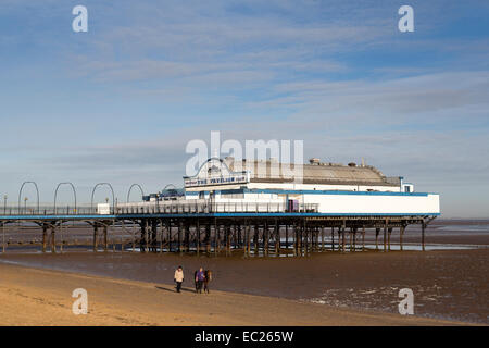 People walking horse on beach with pier at low tide, Cleethorpes, Lincolnshire, England, UK - Stock Photo