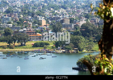 The 4.43 km2-784 ms.high Phewa tal-lake at  foot of the Annapurnas range with Pokhara city seen from the way down - Stock Photo