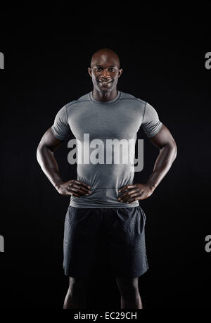 Portrait of happy young African man against black background. Fit young athlete looking at camera smiling with his - Stock Photo