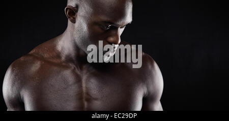 Close-up shot of shirtless African male model with muscular build on black background. Young man with muscular build. - Stock Photo