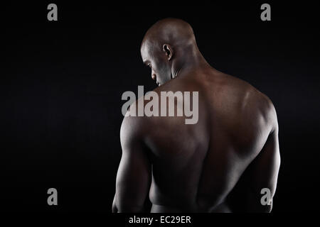 African muscular bodybuilder's back on black background. Shirtless fitness model with copyspace. - Stock Photo