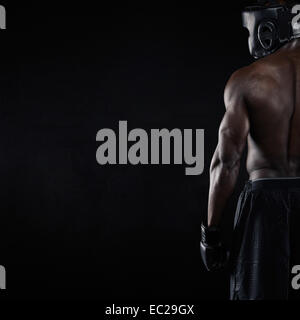 Rear view of muscular young male boxer on black background. Young African male in boxing gear with copy space. - Stock Photo
