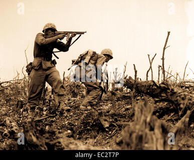 A Marine of the 1st Marine Division draws a bead on a Japanese sniper with his tommy-gun as his companion ducks - Stock Photo