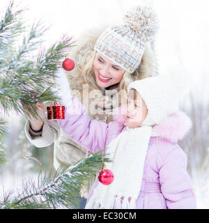 Happy mother and child decorating christmas tree outdoor wintertime - Stock Photo