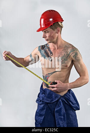 Young fit male shirtless workman with tape measure and safety hat - Stock Photo