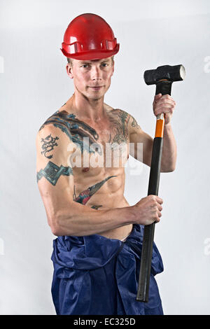 Young fit male shirtless workman with sledge hammer and safety hat - Stock Photo
