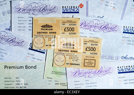 A variety of styles of Premium Savings Bond certificates from 1970s to 2004. - Stock Photo