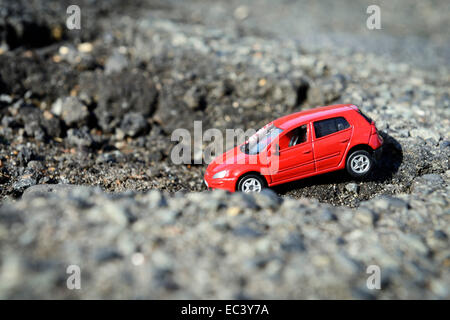 Pothole in a road with miniature car - Stock Photo