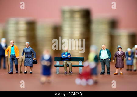 Miniature figures of elderly people and stacked euro coins, pension - Stock Photo