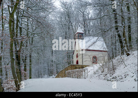 Small wooden church in winter near the german castle Burg Eltz. Touristic path to castle. - Stock Photo