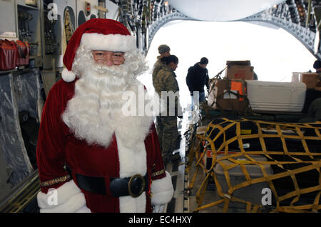 Santa Claus arrives on an Alaska Air National Guard C-17 Globemaster military transport aircraft during a visit - Stock Photo