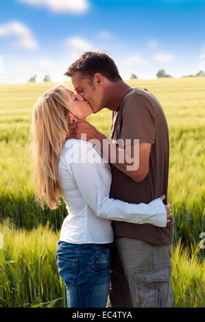 Couple kissing at the edge of a corn field - Stock Photo