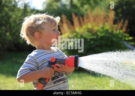 boy with garden shower - Stock Photo
