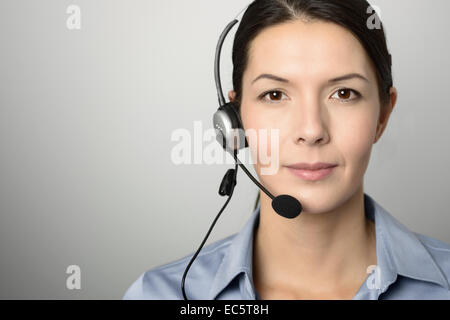 Attractive female call center operator, client services assistant or telemarketer wearing a headset looking at the - Stock Photo